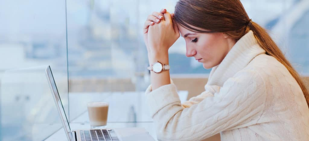 The Stress of Not Writing blog featured image woman holding head next to laptop